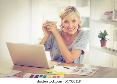 Portrait of a smiling businesswoman working on a laptop at office