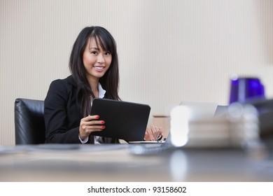 Portrait of smiling businesswoman working on digital tablet