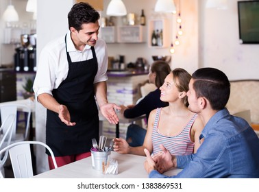 Portrait of smiling cafe waiter standing at table and talking to guests in a cozy cafe