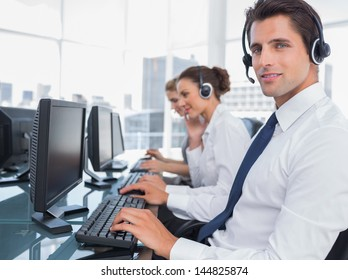 Portrait of smiling call center employee with colleagues behind