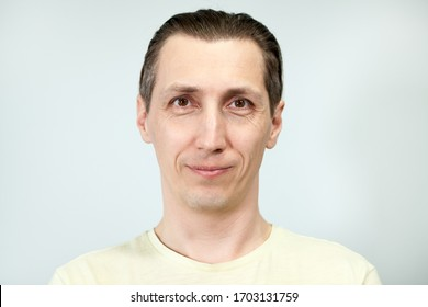 Portrait of a smiling and calm man, grey background, emotions series.