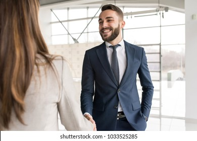 Portrait  of smiling car salesman shaking hands with woman buying new car in dealership showroom