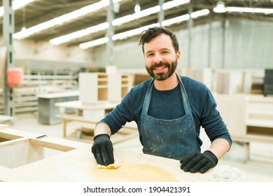 Portrait of a smiling carpenter staining wood with oil stain in his big workshop. Hard-working worker doing his job in a wood shop