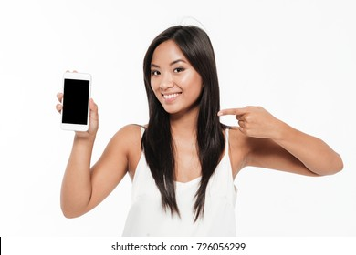 Portrait of a smiling casual asian woman holding and pointing finger at blank screen mobile phone isolated over white background