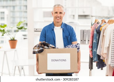 Portrait of smiling casual businessman holding donation box in the office