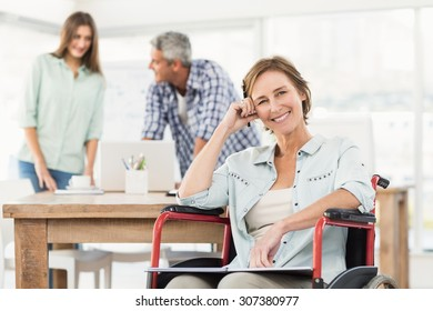 Portrait of smiling casual businesswoman in wheelchair in the office