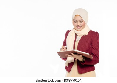 Portrait of smiling casual girl refering schedule in her planner book while standing isolated over white background