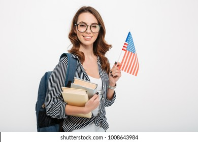 Portrait of a smiling casual girl student with backpack holding books and american flag isolated over white background
