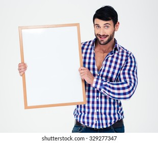 Portrait of a smiling casual man holding blank board isolated on a white background