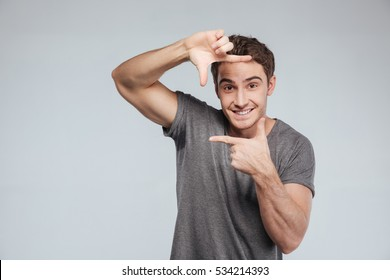 Portrait of a smiling casual man making frame with hands over white background