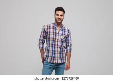 portrait of smiling casual man wearing shirt with blue checkers standing on light grey background