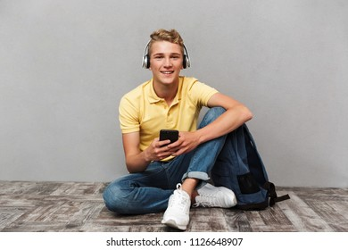 Portrait of a smiling casual teenage boy in headphones with backpack sitting and holding mobile phone isolated over gray background