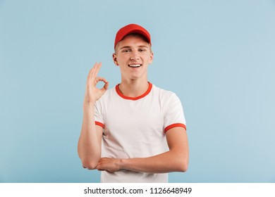 d8526c9b11d Portrait of a smiling casual teenage boy in red cap showing ok gesture  isolated over blue