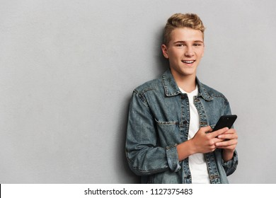 Portrait of a smiling casual teenage boy dressed in denim jacket holding mobile phone isolated over gray background