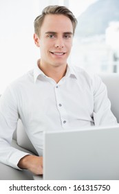 Portrait of a smiling casual young man using laptop on sofa in a bright house