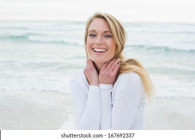 Portrait of a smiling casual young woman standing at the beach