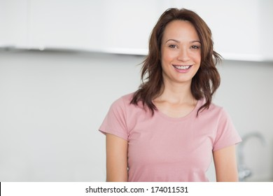 Portrait of a smiling casual young woman in the kitchen at home