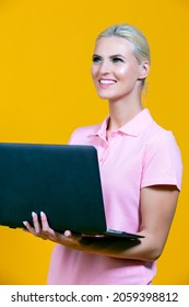 Portrait of Smiling Caucasian Blond Girl with Laptop Posing With Smile Against Colorful Yellow Background. Vertical Orientation