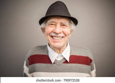portrait of a smiling caucasian elderly man in a black hat