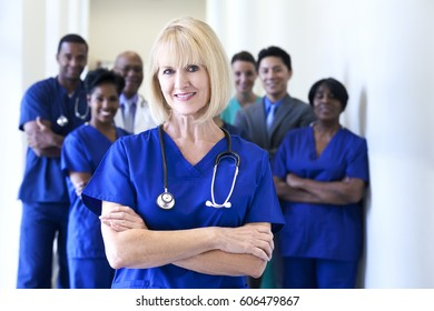 Portrait smiling Caucasian female nurse with dedicated multi ethnic clinical nursing and management team in medical centre