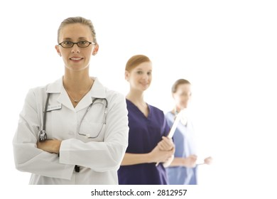 Portrait of smiling Caucasian medical healthcare workers in uniforms standing against white background.