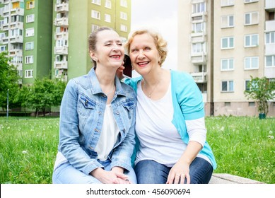 Portrait of smiling caucasian middle aged sisters doing self-ie by white mobile phone outdoor