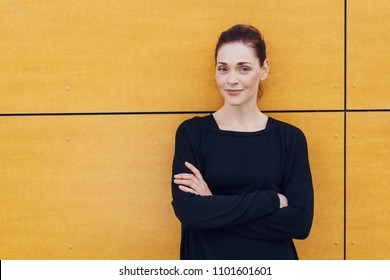 A portrait of a smiling caucasian woman with folded arms leaning against yellow, urban wall.