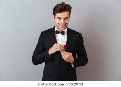 Portrait of a smiling charming man dressed in tuxedo taking out a box with an engagement ring from his jacket isolated over gray background