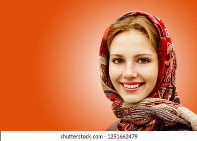 Portrait of smiling charming young woman in headscarf isolated on orange background.
