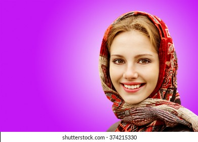Portrait of smiling charming young woman in headscarf on purple background.