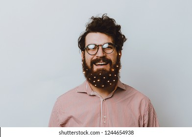 Portrait of smiling cheerful bearded hipster man with christmas lights in beard and wearing glasses over white wall
