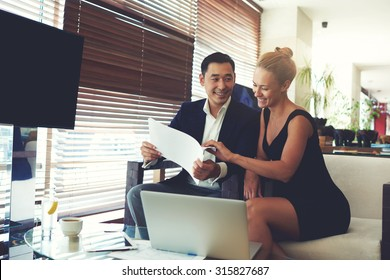 Portrait of a smiling cheerful business men and women watching together working papers while sitting with laptop computer in office space, young happy leadership received good results in their job