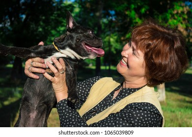 Portrait of smiling, cheerful woman hold, kissing pet, room dog. Black, active, inquisitive french bulldog. Caucasian, elderly mom, housewife looks to dog. Happy summer company on grass in the forest.