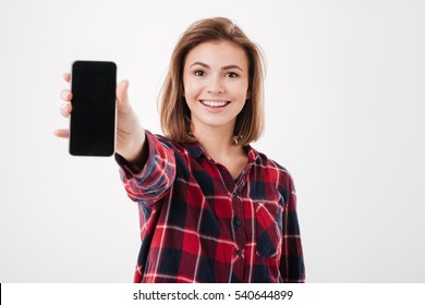 Portrait of a smiling cheerful woman showing blank smartphone screen isolated on a white background