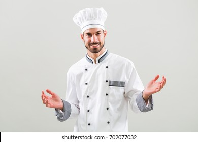 Portrait of smiling chef with arms outstretched  on gray background.Chef gesturing