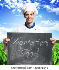 Portrait of a smiling chef holding a blackboard