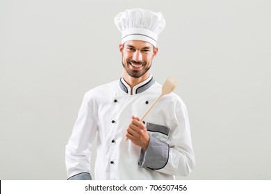 Portrait of smiling chef holding wooden spoon on gray background.Chef with his work tool