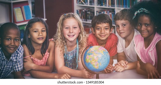 Portrait of smiling children with globe on table in library