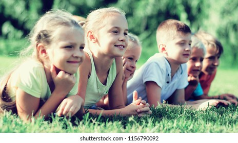 portrait of smiling children lying on grass in park and looking happy