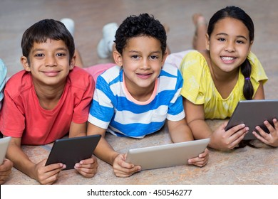 Portrait of smiling children using digital tablets while lying on floor