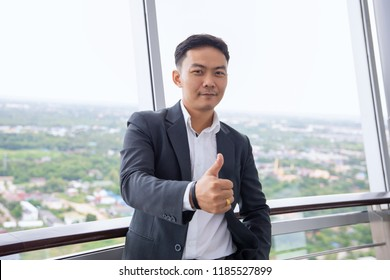 portrait of smiling chinese businessman  show thumb up on the top of building