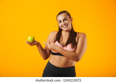 569ba7d521 Portrait of smiling chubby woman in sportive bra holding apple isolated  over yellow background