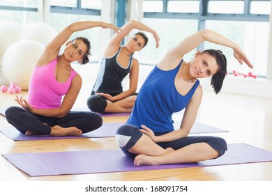 Portrait of smiling class and instructor doing stretching pilate exercises in fitness studio