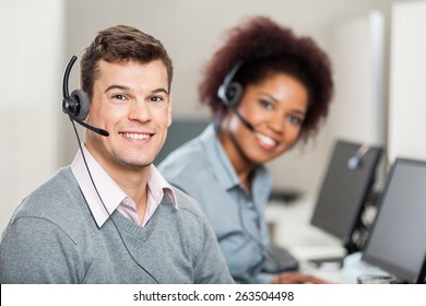 Portrait of smiling colleagues working in call center