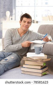 Portrait of smiling college student learning at home with pile of books, sitting on floor, taking notes, looking at camera.?