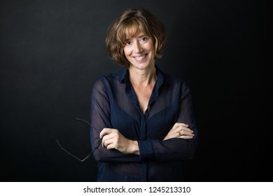 Portrait of smiling confident adult woman smiling and looking at camera with eyeglasses in hands over black background.