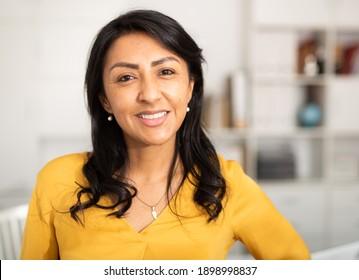 Portrait of smiling confident hispanic woman employee posing in light office interior