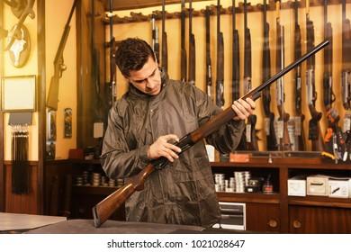 Portrait of smiling confident man in gun shop showing rifle