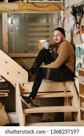 Portrait of smiling, confident, strong, handsome, middle aged, bearded carpenter in a watch cap. His hands crossed over chest. Sitting on a handmade stairs. Drinking his coffie.
