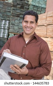 Portrait of a smiling confident supervisor stock taking in warehouse